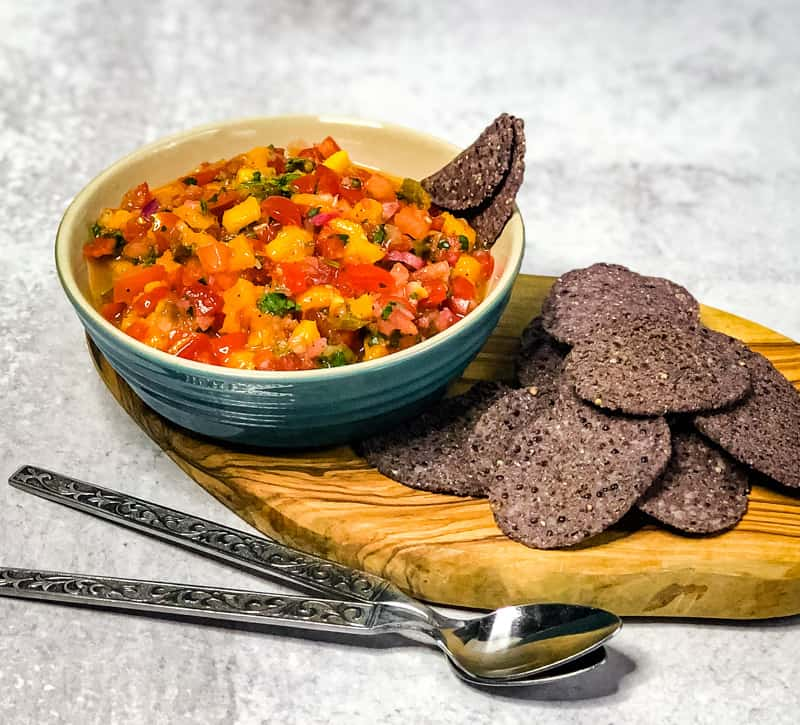 Mango Salsa in a blue bowl on small wood cutting board garnished with blue corn tortilla chips.