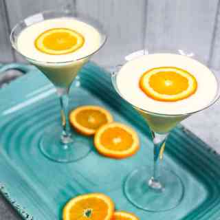 Overhead shot of two Creamsicle Martinis on an aqua colored tray with orange slices for garnish.