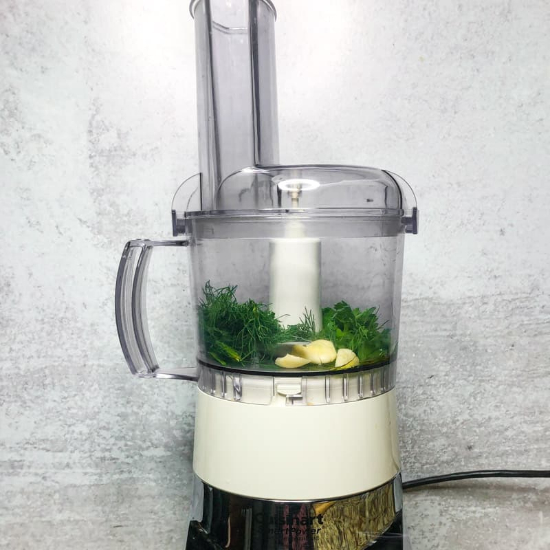 Herbs, garlic, and oil in the bowl of a food processor.