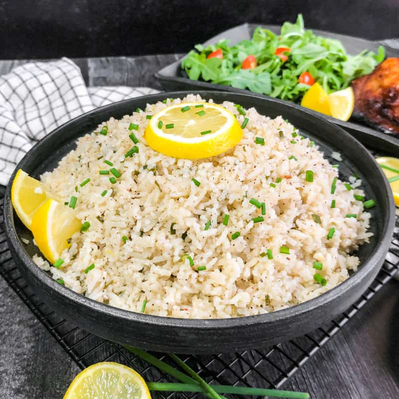 Close up of Coconut Rice in a black bowl, garnished iwth lemon and chives with a blurred salad and chicken in the background.