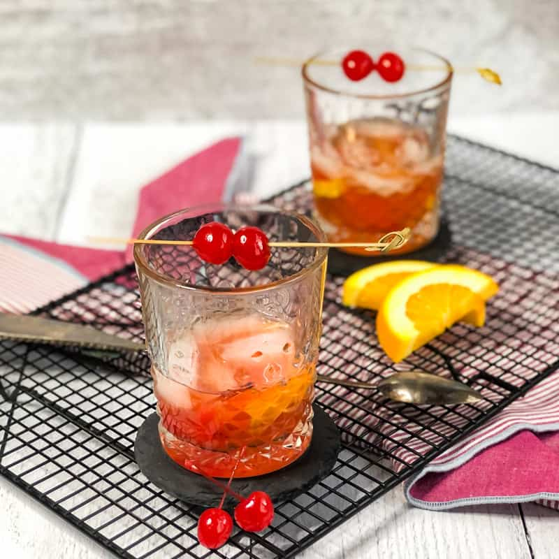 Overhead shot of two old fashioned cocktails on a wire rack garnished with cherries and orange slices.