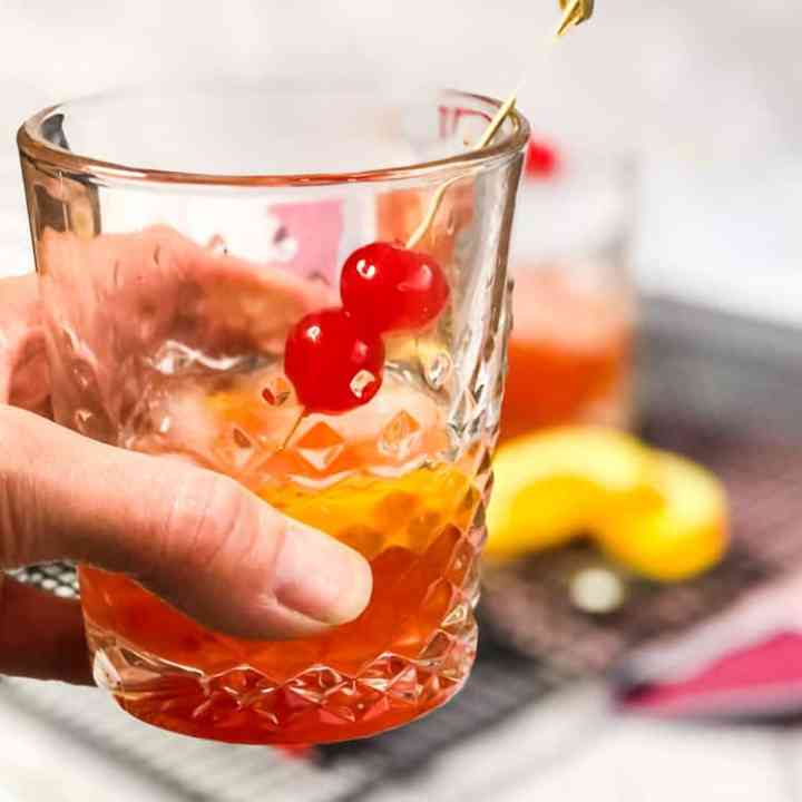 Hand holding a Peanut Butter Whiskey Old Fashioned garnished with additional cherries.