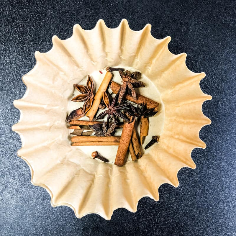 Toasted spices in a coffee filter, ready to be tied into a bundle.
