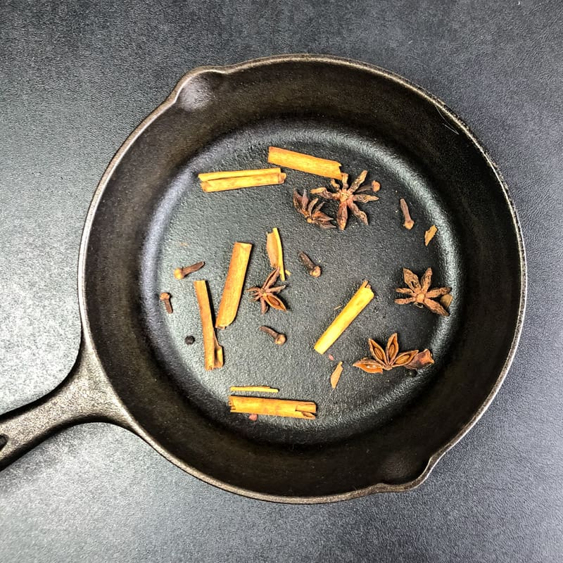 Cinnamon, cloves, and star anise in a small cast iron skillet ready to be toasted.