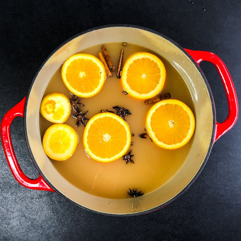 Overhead shot of apple cider in a Dutch oven with sliced oranges and spices floating.