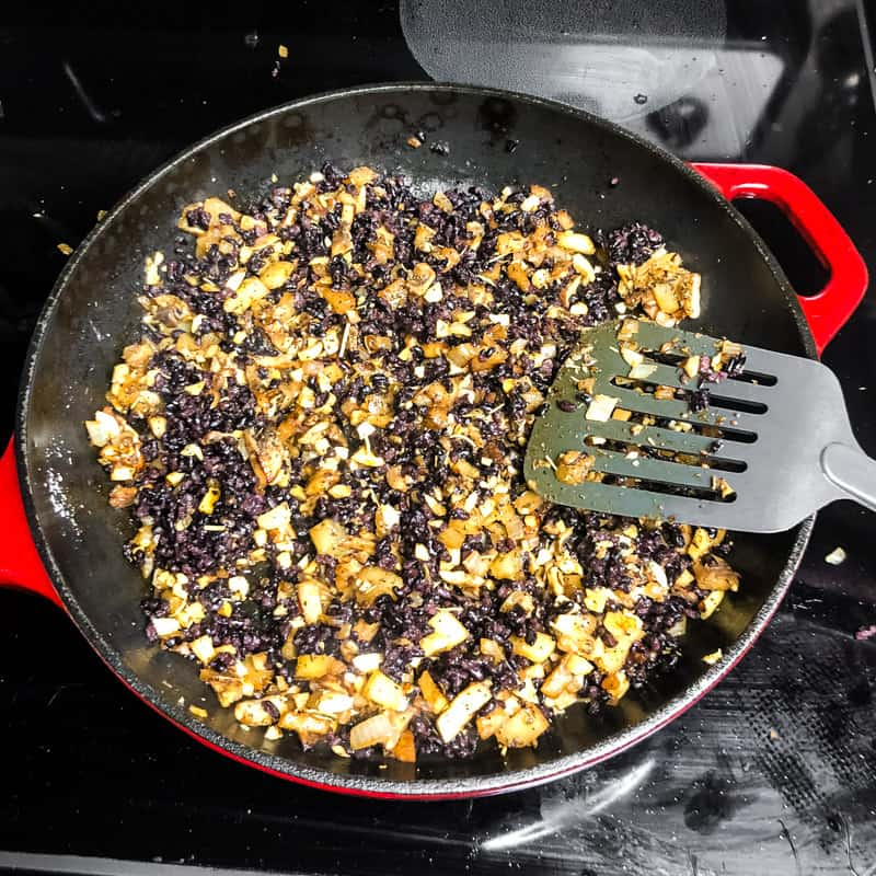 Rice, parmesan cheese, and almonds added to the skillet.