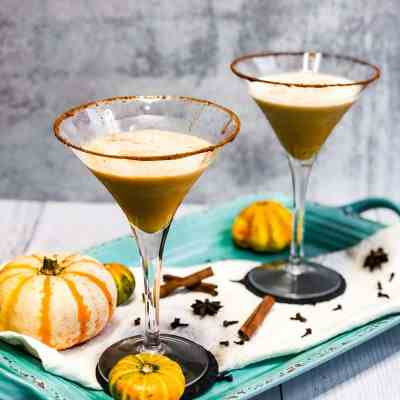 Side shot of Pumpkin Spice Martinis on a blue tray garnished with small pumpkins.