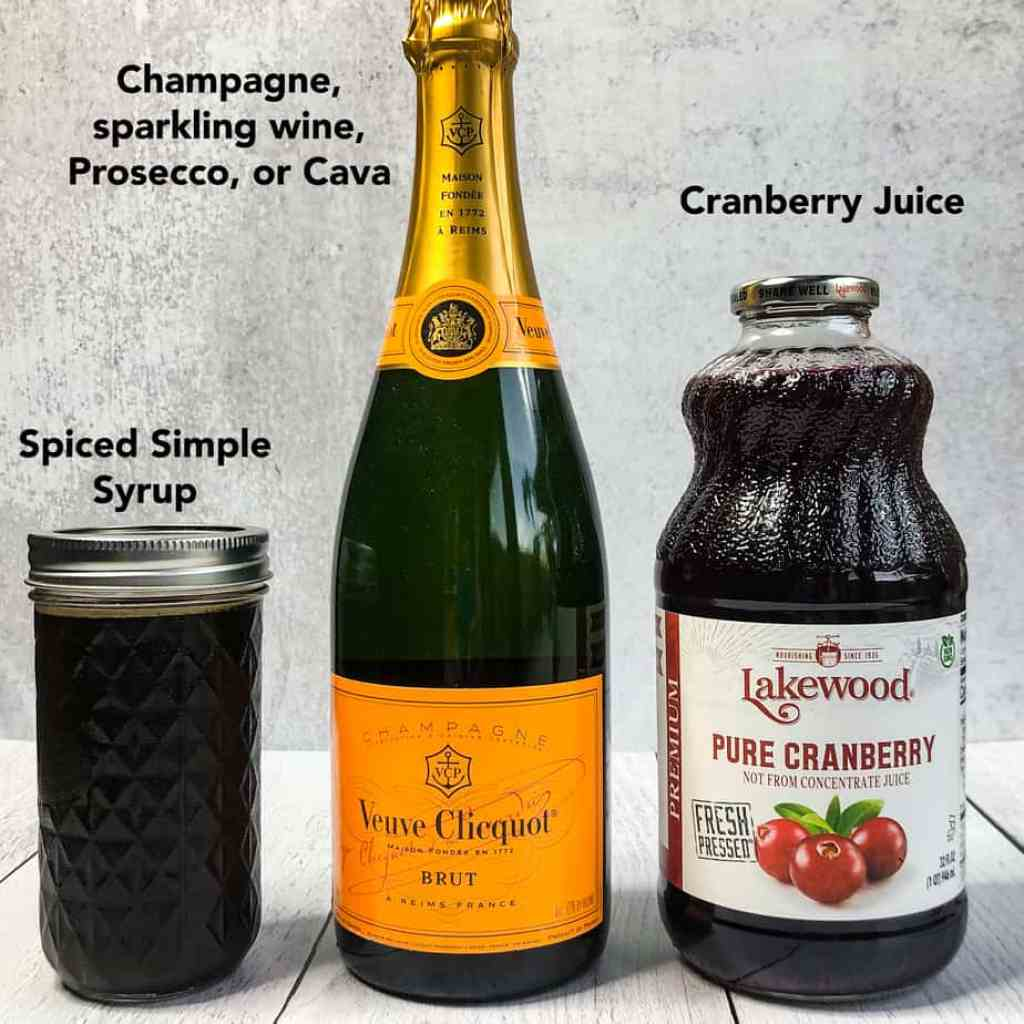 Bottle of cranberry juice, champagne, and jar of spiced simple syrup.