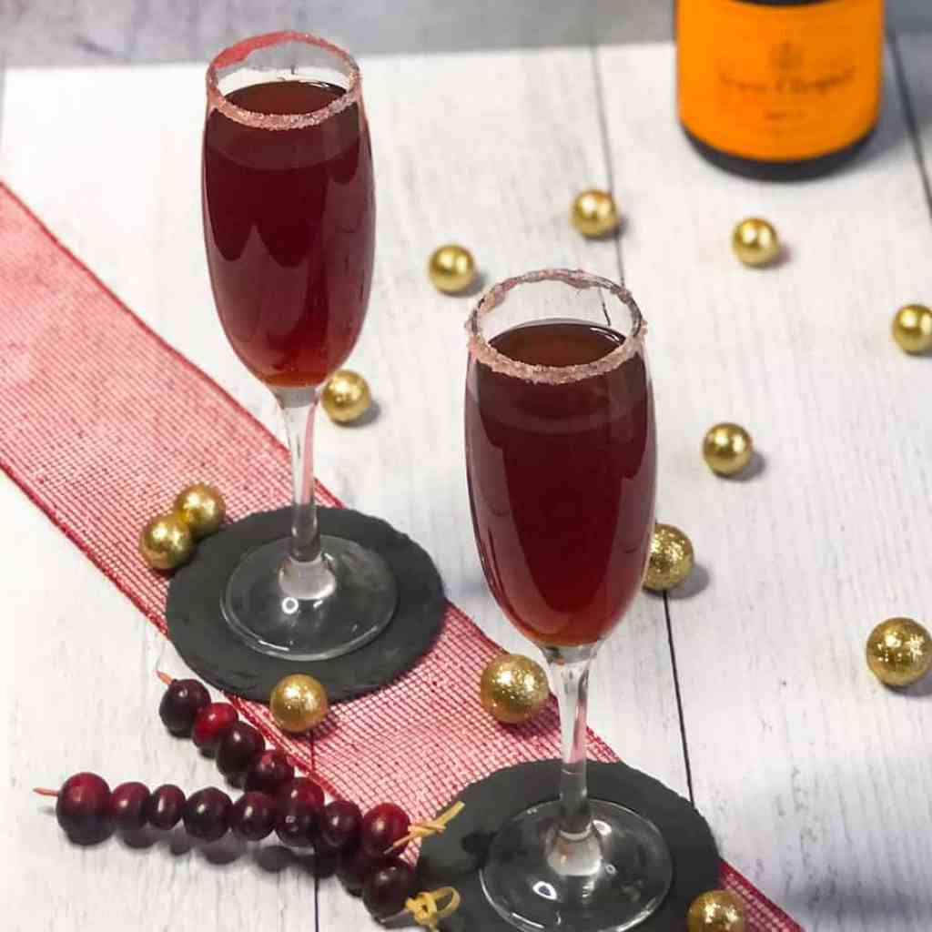Overhead shot of Cranberry Mimosas on a red ribbon with cranberries and gold balls below.