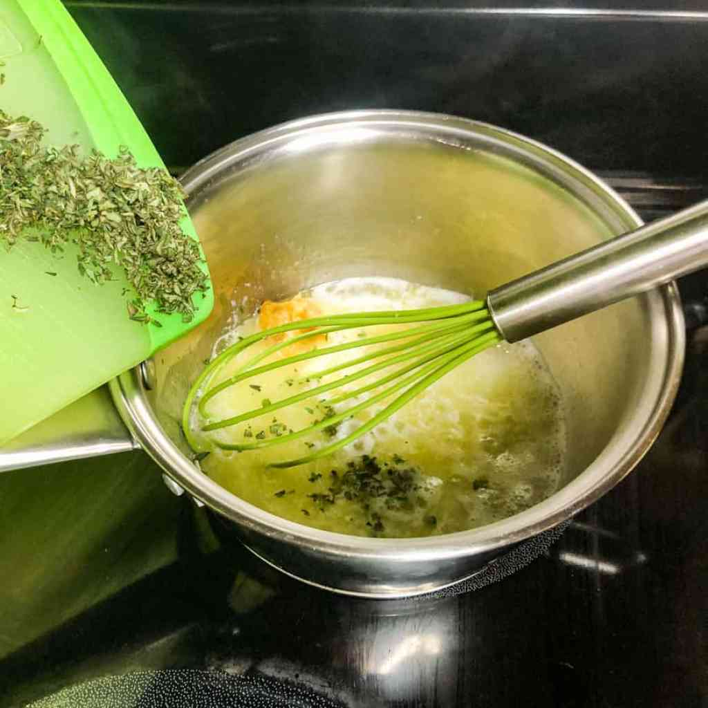 Herbs being added to the melted butter mixture.