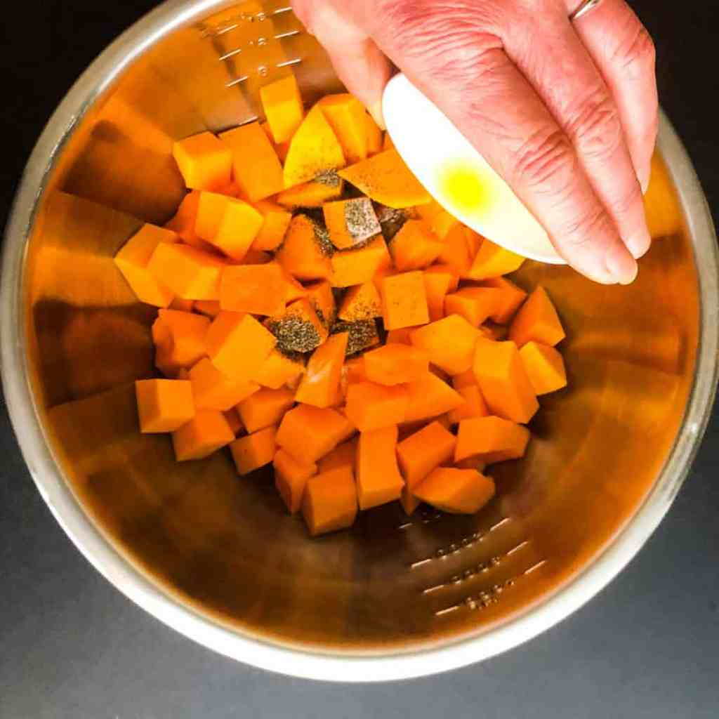 Diced squash in a stainless steel bowl with hand pouring in olive oil.