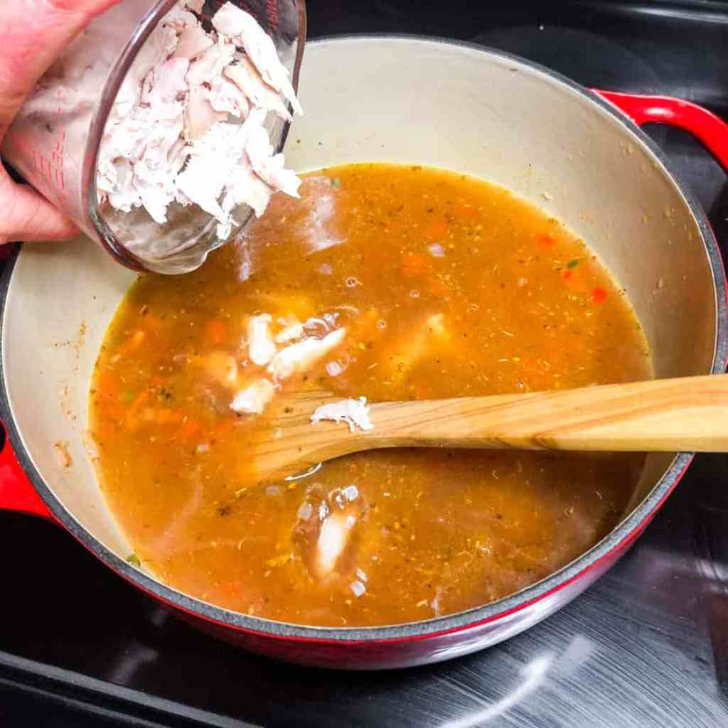 Adding shredded chicken to the Dutch oven.