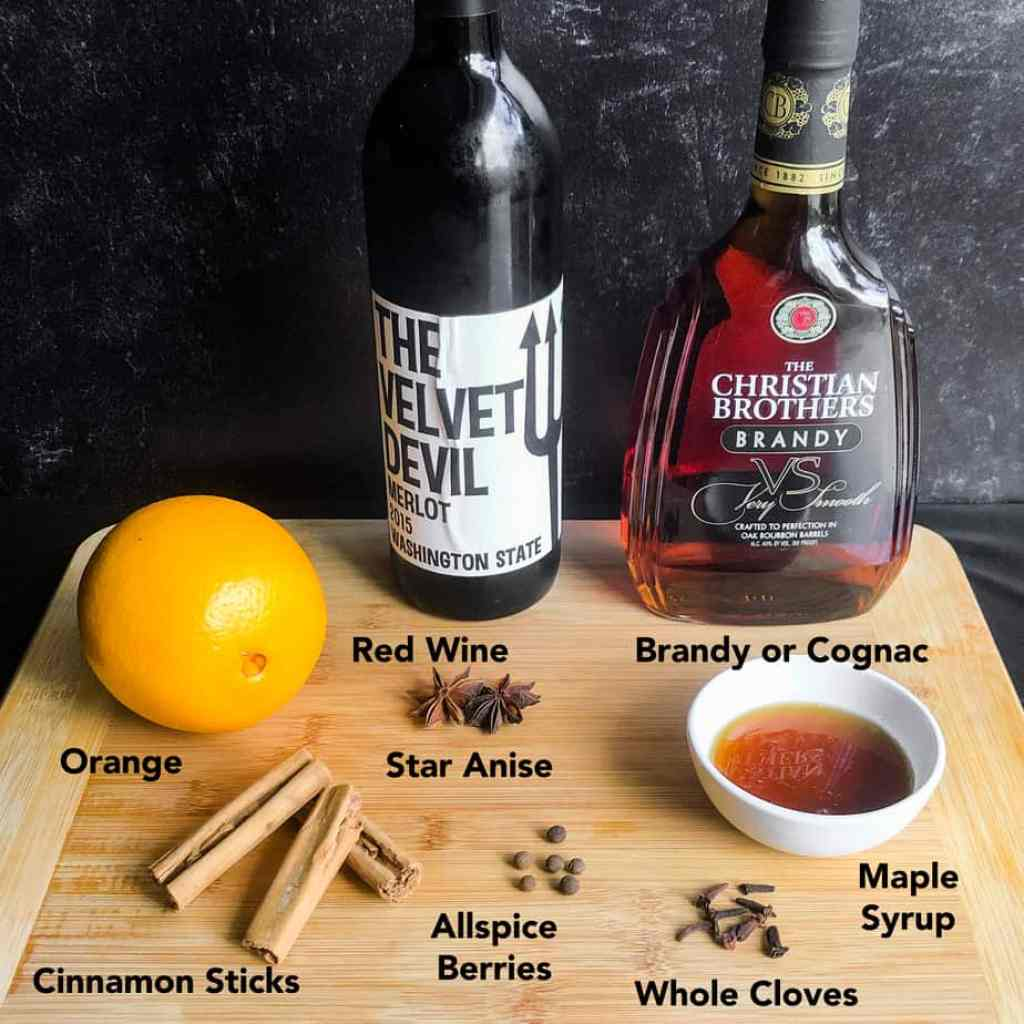 Ingredients for mulled wine on a wood cutting board: merlot, brandy, orange, cinnamon, star anise, cloves, allspice berries, and maple syrup.