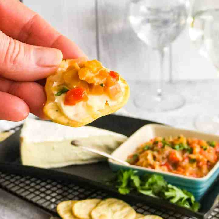 Hand holding a cracker topped with brie cheese and chutney with a bowl of chutney and block of brie blurred in the background.