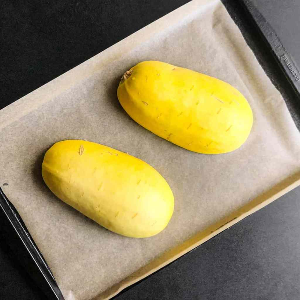Spaghetti squash halves on a baking sheet lined with parchment paper.
