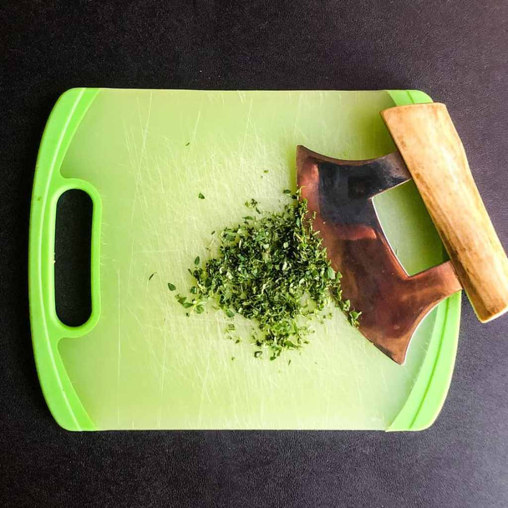 Fresh thyme finely chopped on a green cutting board with ulu knife resting beside.