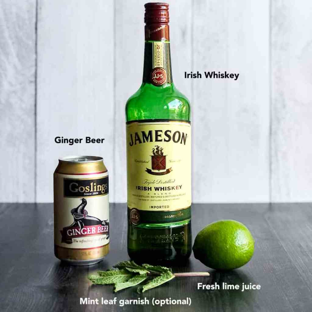 Mint leaves, lime, bottle of Irish whiskey, and can of ginger beer.