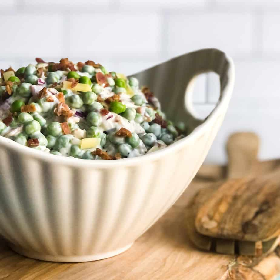 Pea Salad garnished with bacon bits in a white bowl.