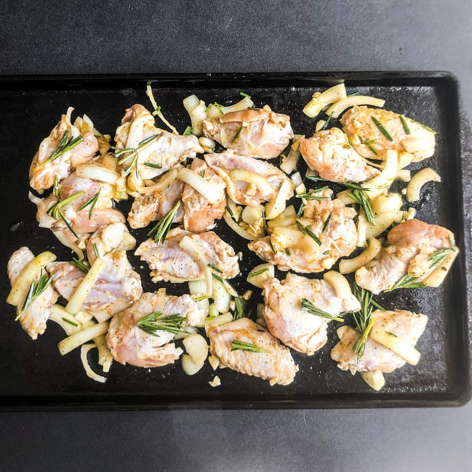 Wings, onion, garlic, and rosemary spread on a dark baking sheet ready to go on the smoker.