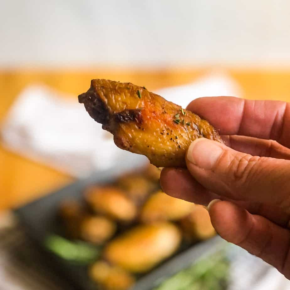 Closeup of a hand holding a smoked chicken wing.