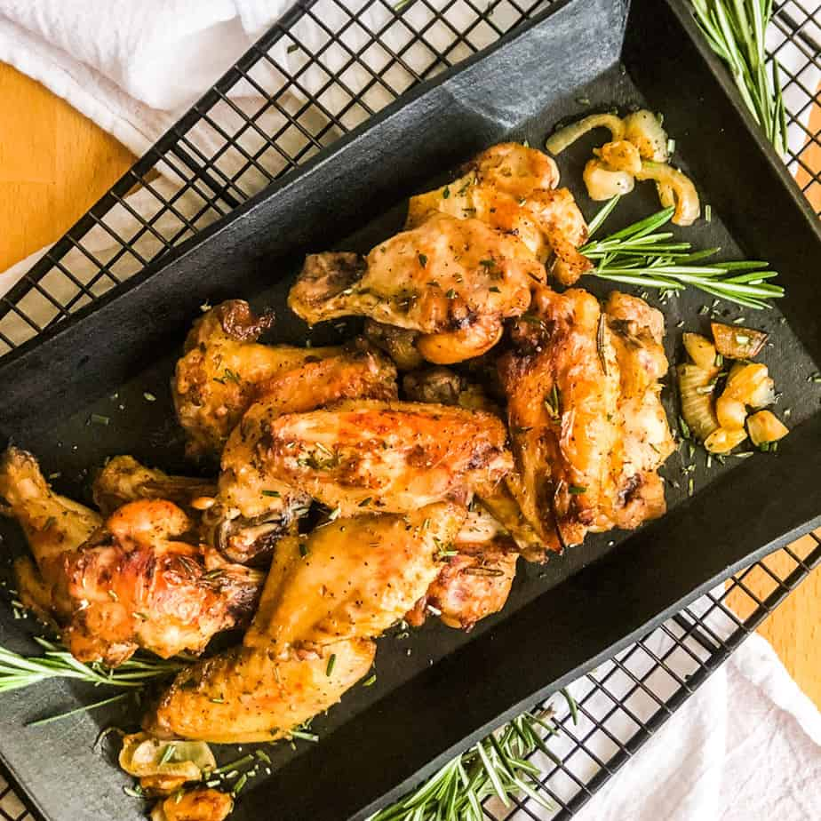 Overhead shot of Crispy Smoked Chicken Wings on a black platter garnished with fresh rosemary.