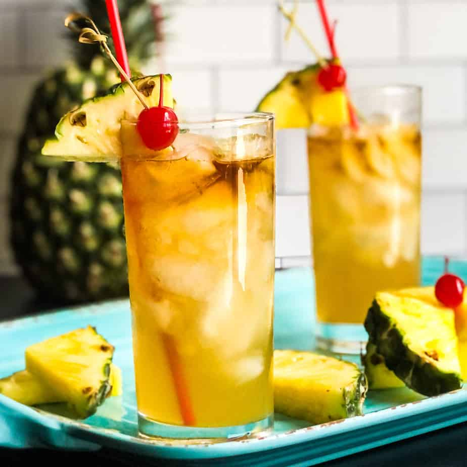 Mai Tai cocktail in a highball glass garnished with a pineapple wedge and cherry.