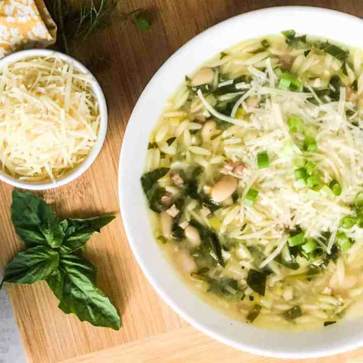 Close up of Orzo Soup with basil leaves and bowl of parmesan to the right.