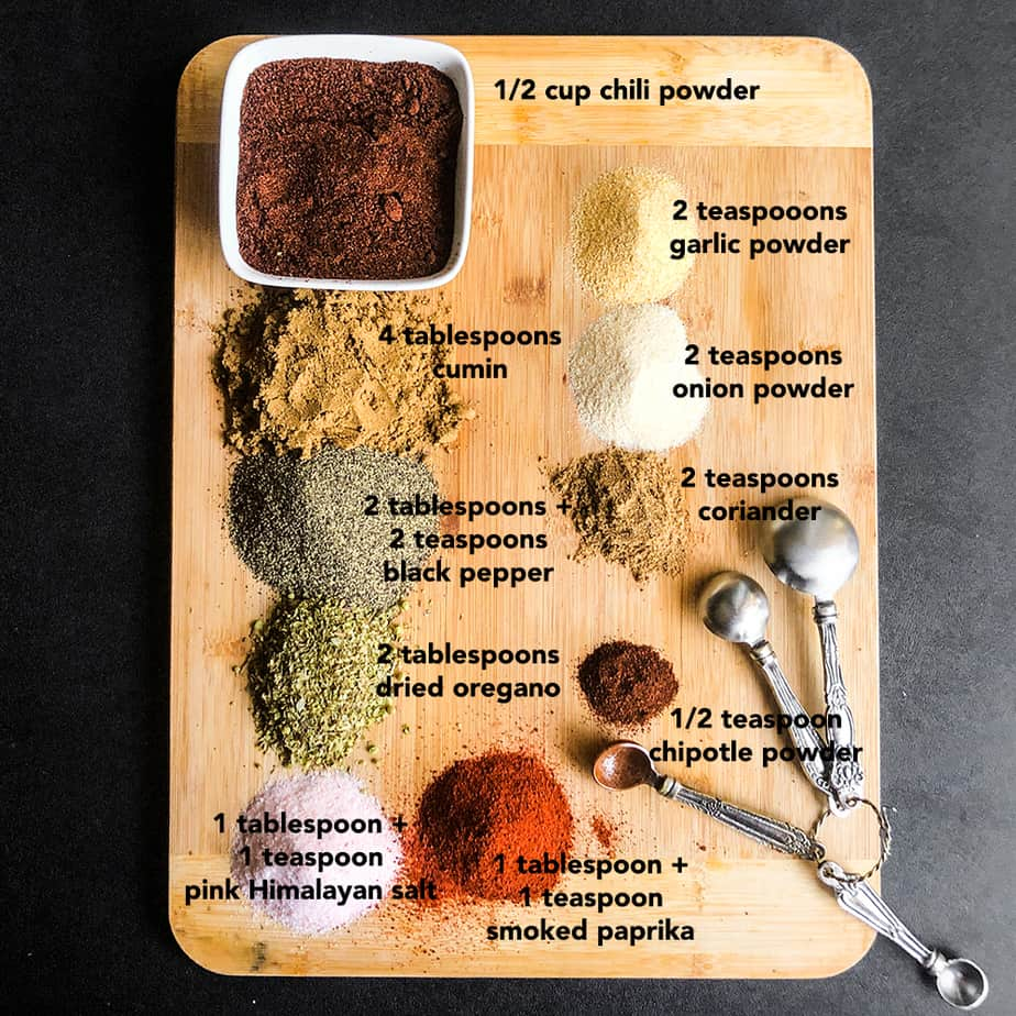 Spices portioned on a wood cutting board.