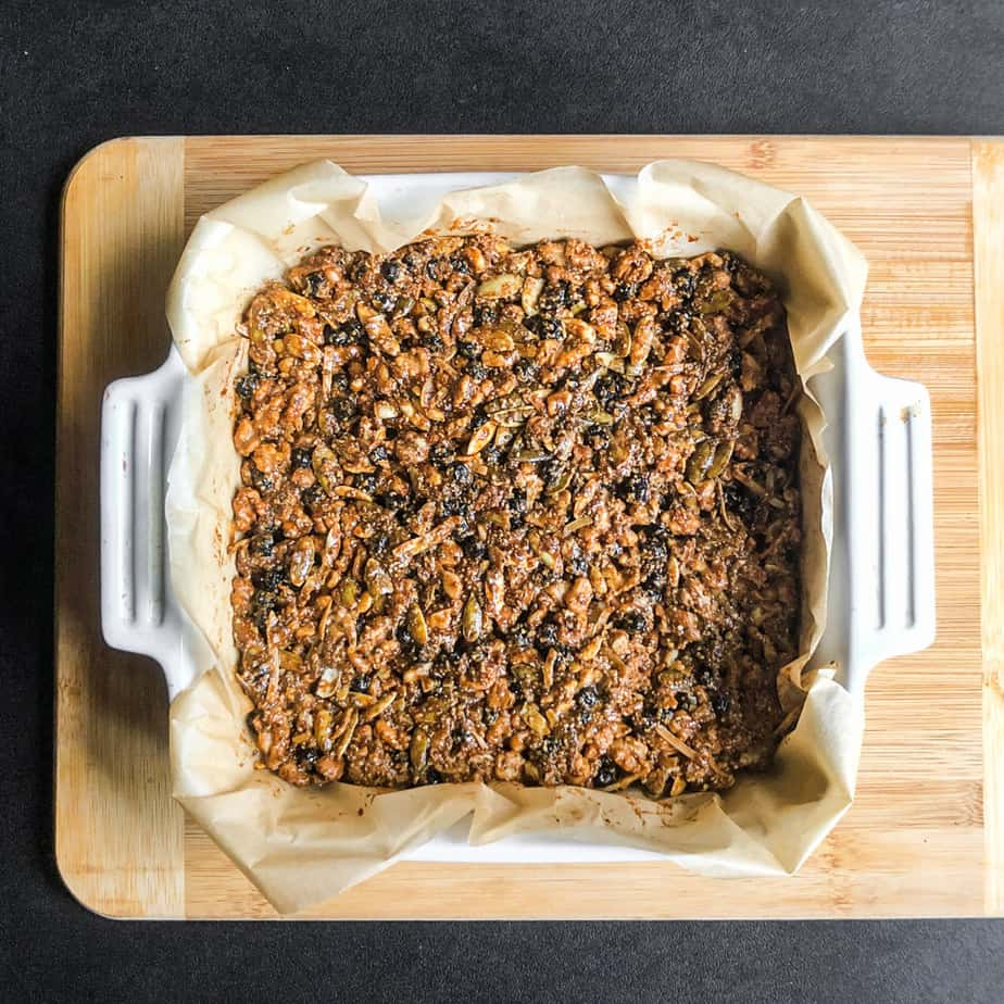 Cooked Walnut Bars in a square baking dish on a wood cutting board.