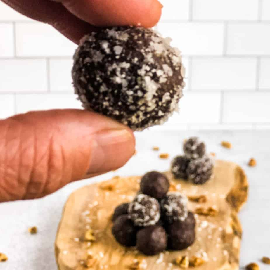 Fingers holding a walnut date ball coated in coconut flakes with a stack of more walnut balls blurred in the background.