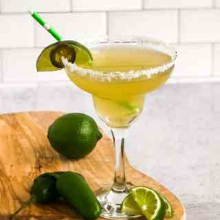 Close up of Pineapple Jalapeno Margarita in a salt rimmed glass garnished with a lime wedge and jalapeno slice.