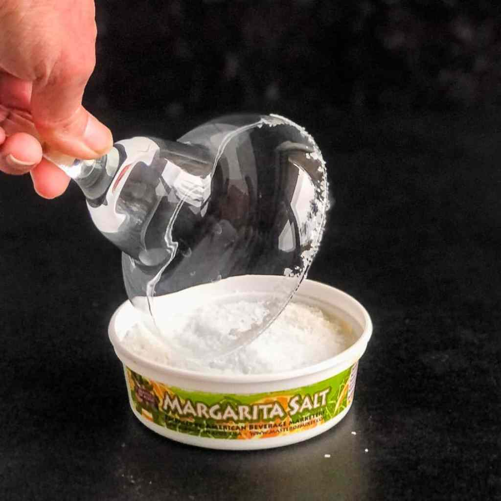Hand dipping a margarita glass into margarita salt.