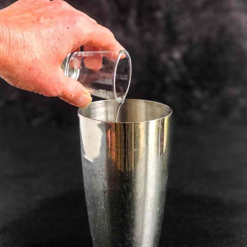 Hand pouring orange liqueur into a cocktail shaker.