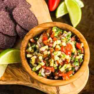 Overhead shot of Pineapple Pico de Gallo in a wood bowl surrounded by tortilla chips and lime wedges.