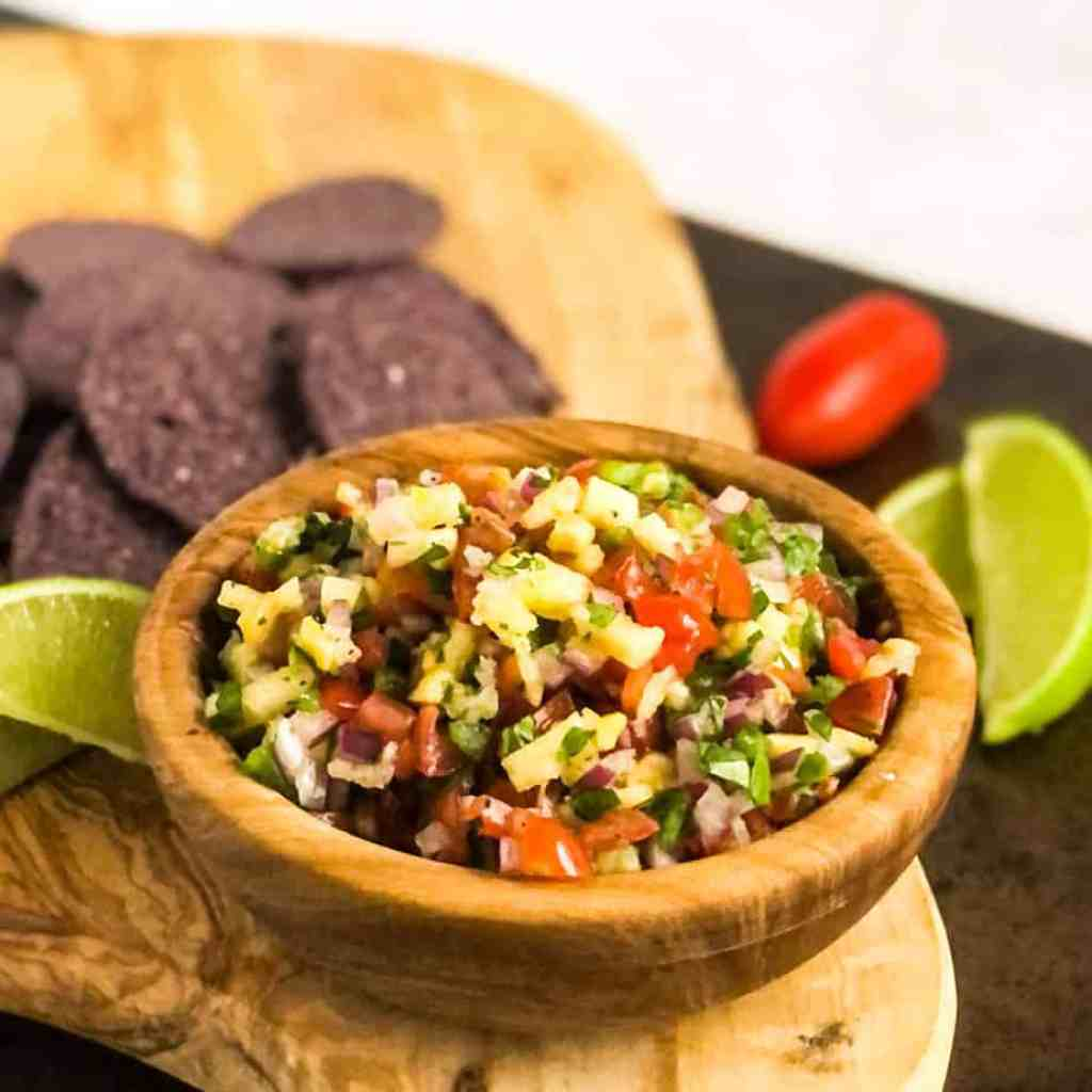Pico de gallo in a wood bowl on a wood cutting board with tortilla chips blurred in background.