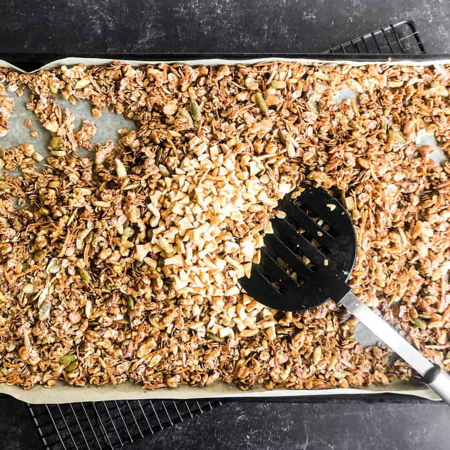 Spatula stirring dried apple pieces into a sheet of cooked granola.