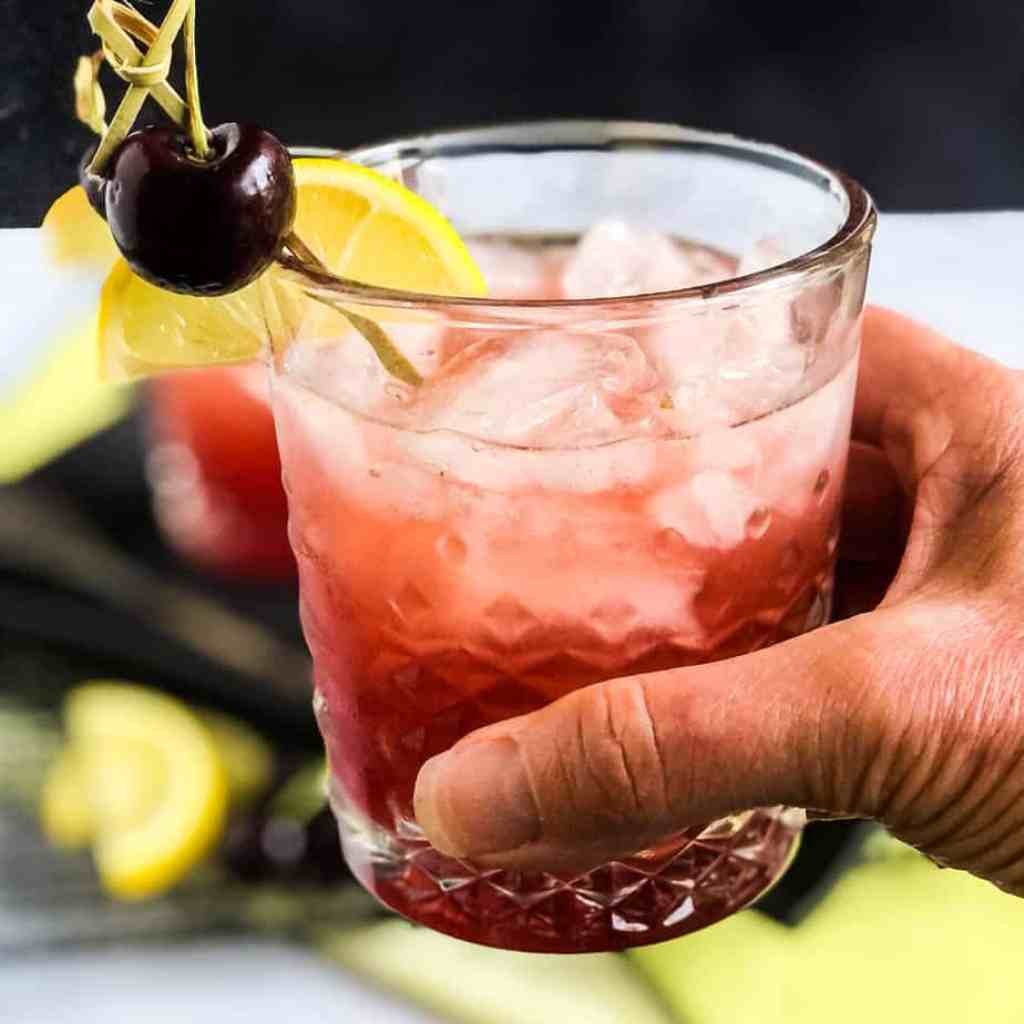 Hand holding a Cherry Bourbon Smash in a cheers salute.