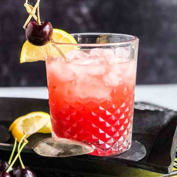 Close up of a single Cherry Bourbon Smash garnished with a lemon wheel and cherry.
