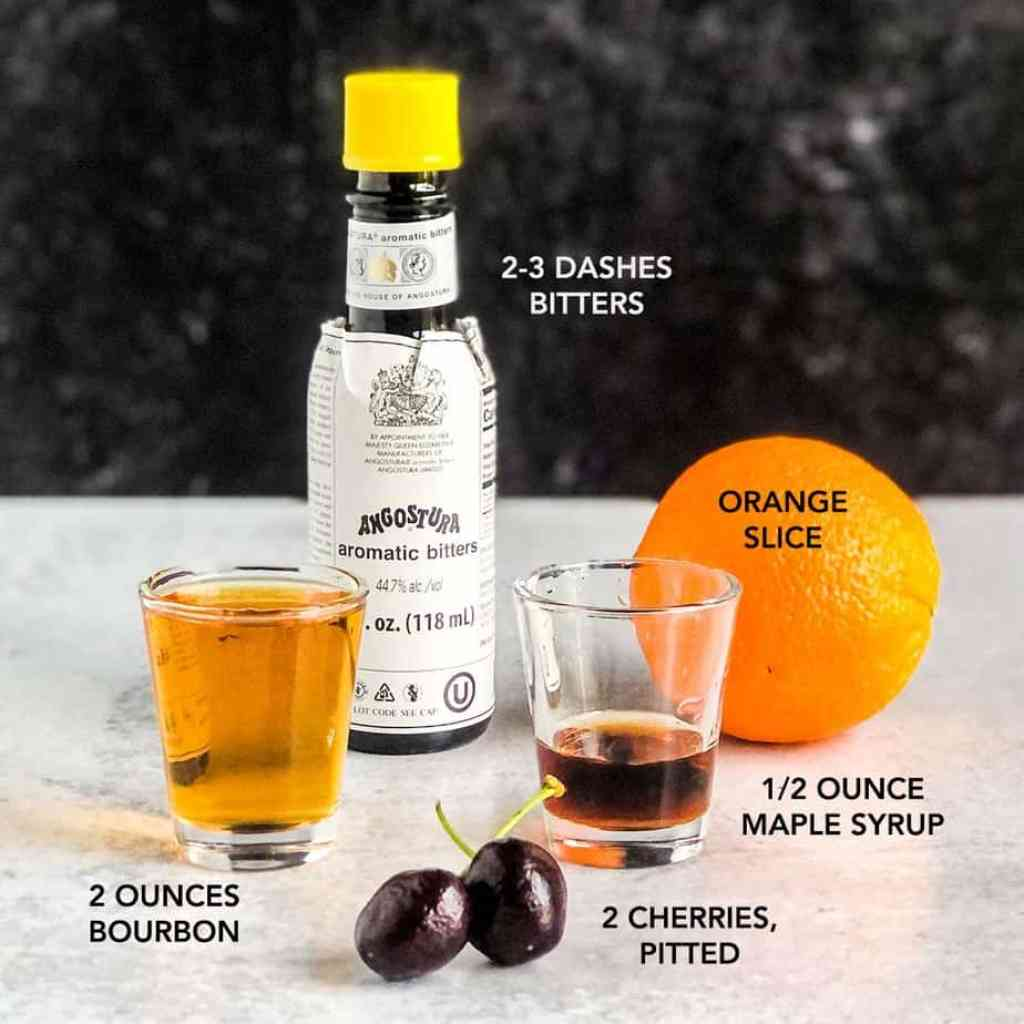 Ingredients for Cherry Maple Old Fashioned portioned on concrete surface with dark background.