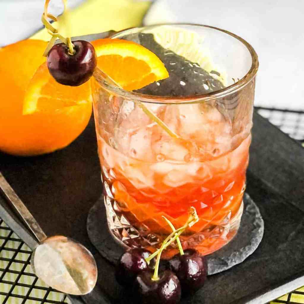 Overhead shot of Maple Syrup Old Fashioned garnished with an orange slice and cherry on a black serving platter.
