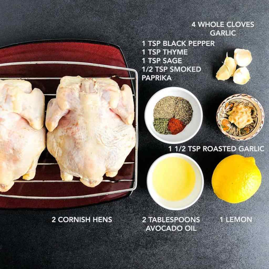 Ingredients for Cornish hens portioned on a black surface.