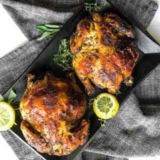 Overhead shot of two Cornish hens on a black platter.