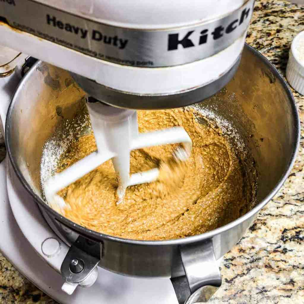 Stand mixer combining one cup of flour into the dough.