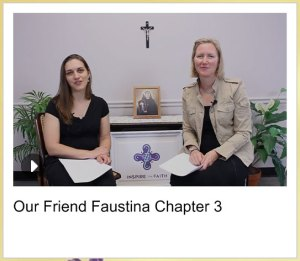 Michele and Emily sitting in front of the book and a crucifix