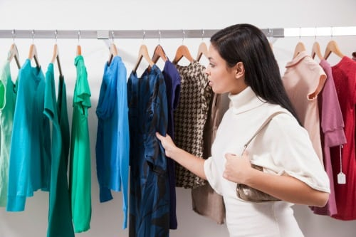 Woman in store looking at colored tops - Saving Your Family Money On Clothing