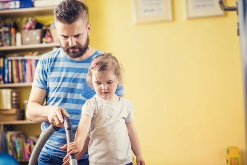 Father vacuuming with Daughter