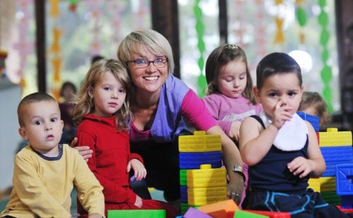 children stacking blocks at Library with teacher