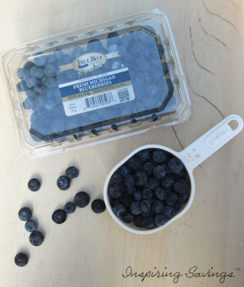 Fresh Blueberries in container with loose blueberries on table