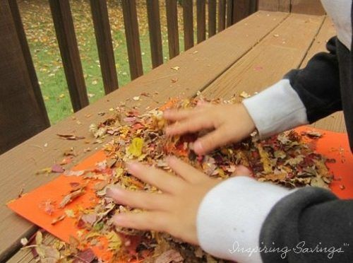 Kids taking crushed leaves and covering art project