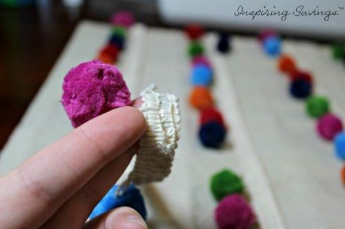 Attaching rows of pom poms to pillow fabric cover
